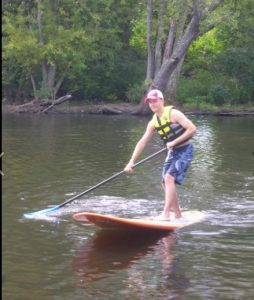 Young Man Paddle Boarding on River Water