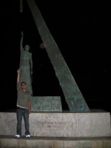 Man Mimicking the Pose of Large Statue Behind Him at Night