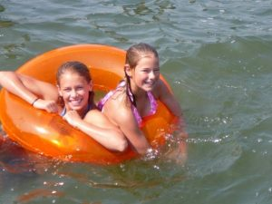 Two Girls on a Floating Tube in the Lake