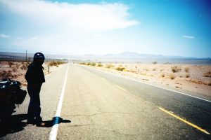 Motorcyclist Standing on Edge of Desert Highway