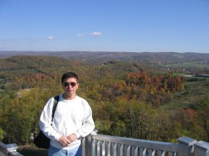 Man Standing Above Sprawling and Hilly Autumn Landscape