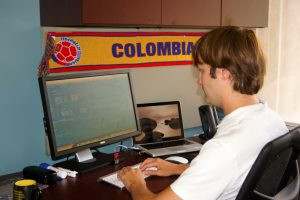 Man Working on Desktop Computer with Colombia Scarf Displayed