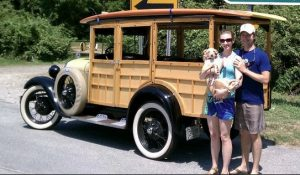 Couple Standing in Front of Antique Car Holding Adorable Dog