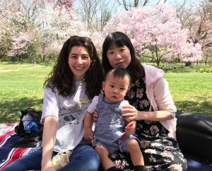 Two Women and Baby Sitting on a Blanket in a Park Celebrating Hanami