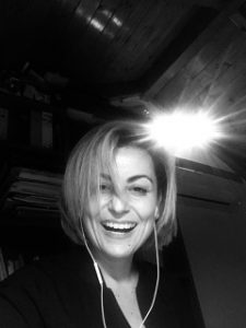 Black and White Image of Eleftheria Hatzmichael with Ear Buds and Laughing