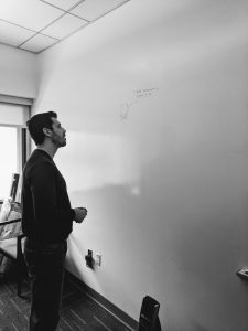 Black and White Image of Man Gazing at Single Drawing on Whiteboard